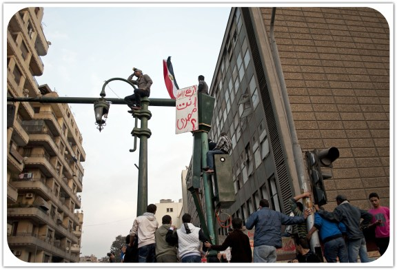 "Youth watch nearby clashes atop a street lamp holding a sign that reads: ""raise your head, you are Egyptian"". November 2011. Photo: Ali Mustafa"